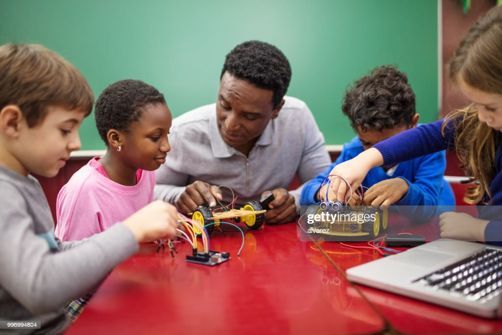 Teacher and students making project in classroom : Stock Photo