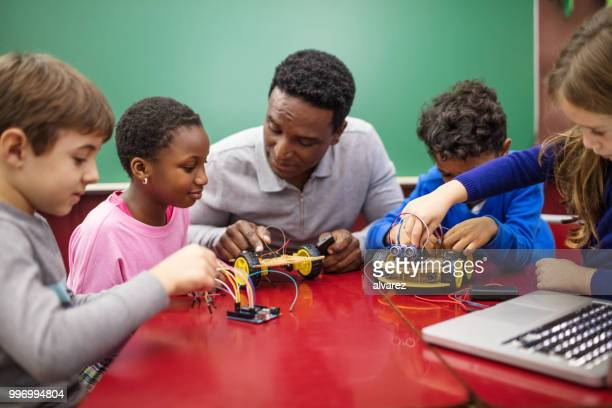 Teacher and students making project in classroom