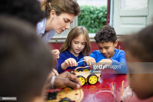 Teacher and students making science project