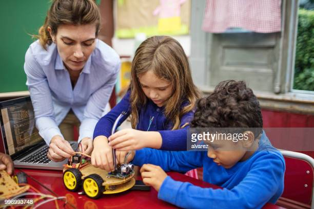 Teacher and students making toy car in class