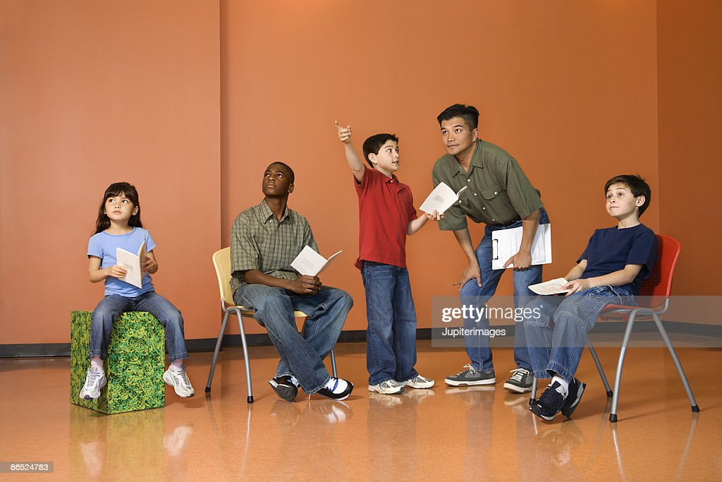 Teacher and students practicing a play : Stock Photo