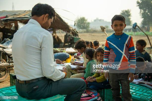 Teacher and students sit on the vegetable crates while studying. Farmers have arranged private teachers to teach their children amid closure of...