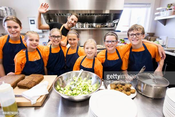 Teacher and students smiling in cooking class