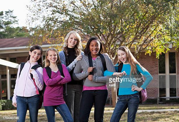 Teacher and students standing outside school