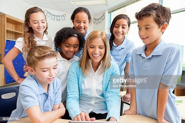 教師と生徒は、クラスプロジェクトにデジタルタブレットを使用します - 男子生徒 ストックフォトと画像