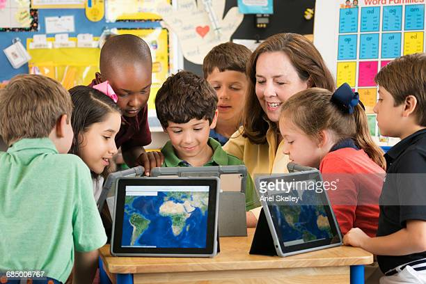 teacher and students using digital tablets in classroom - physical geography stock pictures, royalty-free photos & images
