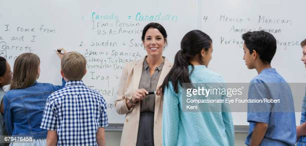 Teacher and students using white board in classroom