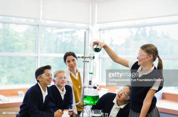 Teacher and students working in chemistry lab