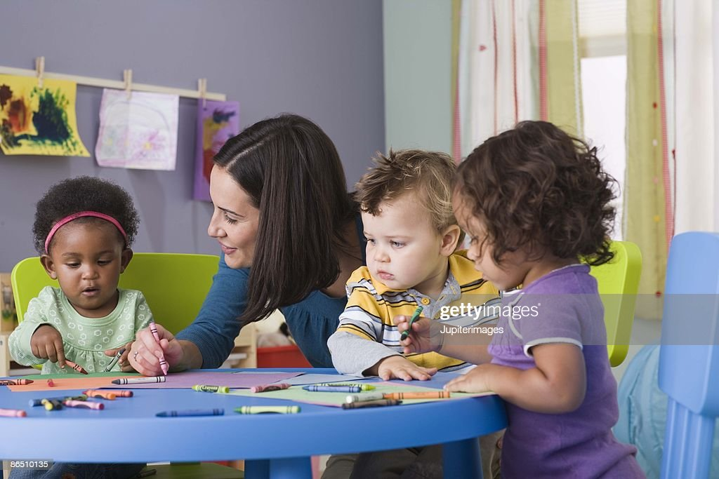 Teacher and toddlers in daycare : Stock Photo