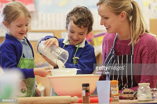 teacher and two primary students cooking - primary age child stock pictures, royalty-free photos & images