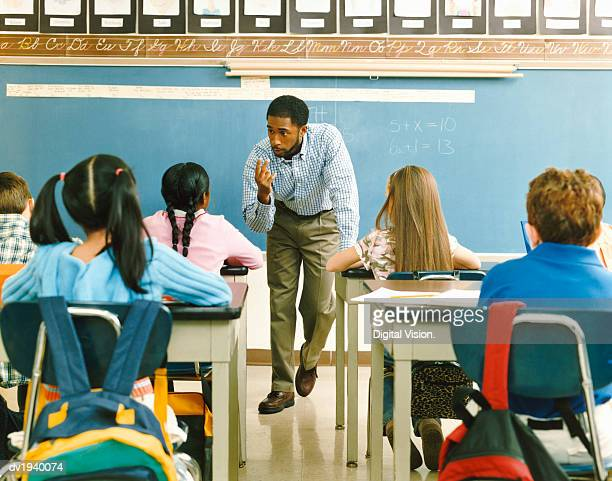 teacher answering a girl in a primary school class - teacher bending over stock photos and pictures