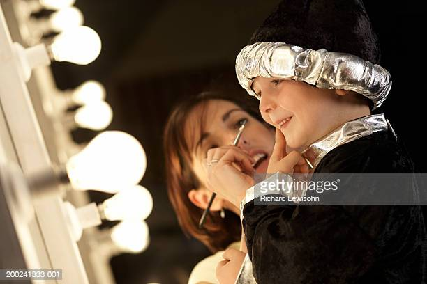teacher applying make-up to boy (3-5) in wizard costume backstage - dietro le quinte palcoscenico foto e immagini stock