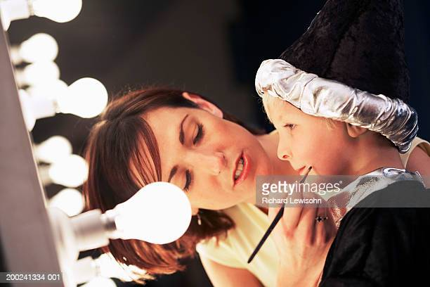 teacher applying make-up to boy (3-5) in wizard costume backstage - school play stock photos and pictures