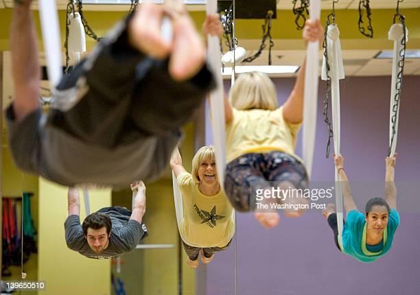 Teacher Arja Pirinen shows students John Fritz and Ana Martinez a swing movement during a zerogravity yoga class at Crunch Fitness in Washington DC...