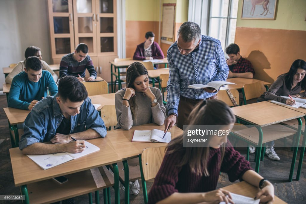 Teacher assisting a female student with studying in the classroom. : Stock Photo