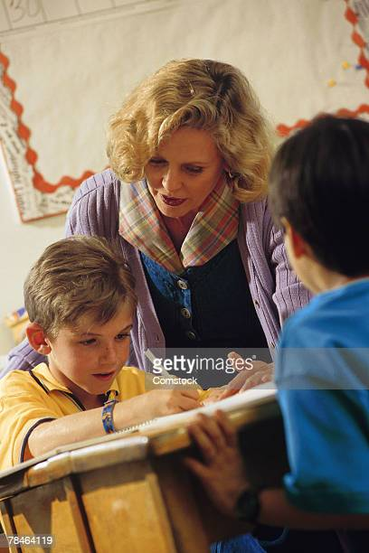teacher assisting a student in the classroom - teacher bending over stock photos and pictures