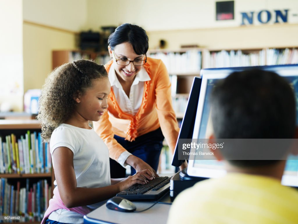 Teacher assisting female student at computer : Stock Photo