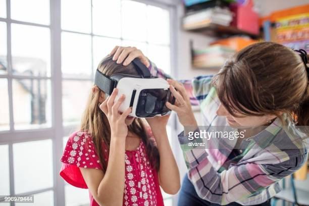 Teacher assisting girl with VR glasses in class