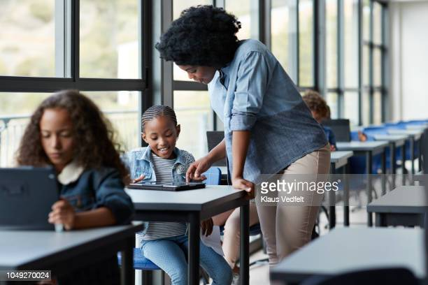 teacher assisting girls in classroom - instructor stock pictures, royalty-free photos & images