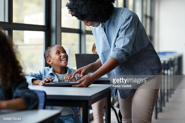 teacher assisting girls in classroom - enseignante photos et images de collection