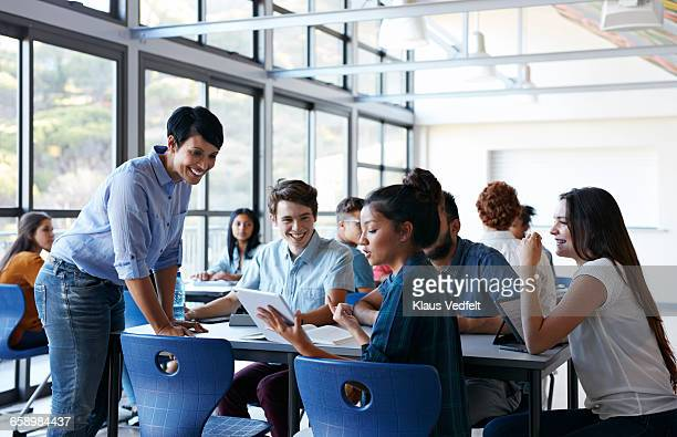 teacher assisting group of students in classroom - academy stock pictures, royalty-free photos & images