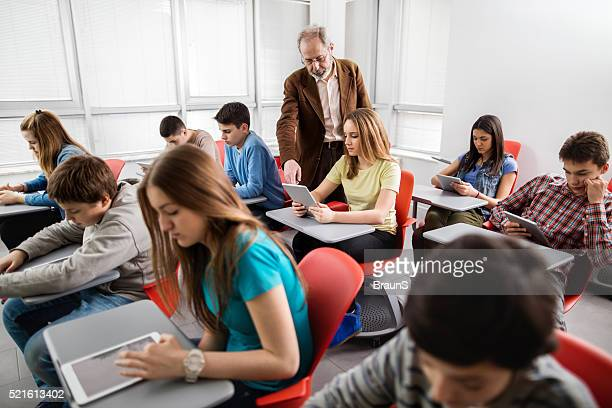 Teacher assisting high school student in a modern classroom.