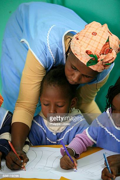 teacher assisting kindergarten students - senegal stock pictures, royalty-free photos & images