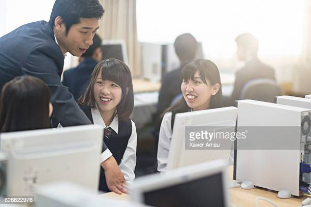 Teacher assisting school girls in computer lab
