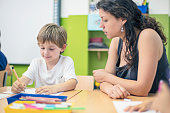 teacher assisting schoolboy drawing paper at
