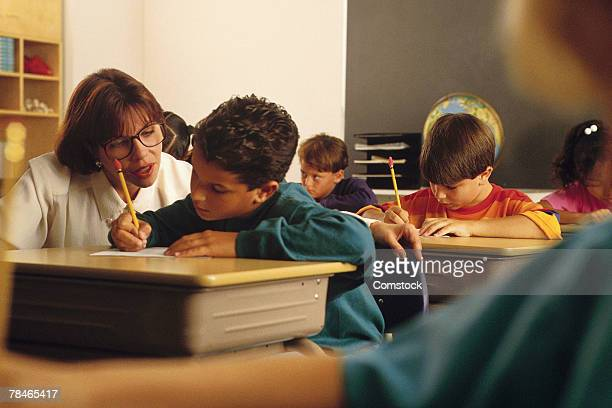 teacher assisting student as others work independently - 20th century stock pictures, royalty-free photos & images