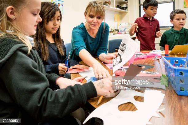 Teacher assisting students in art class