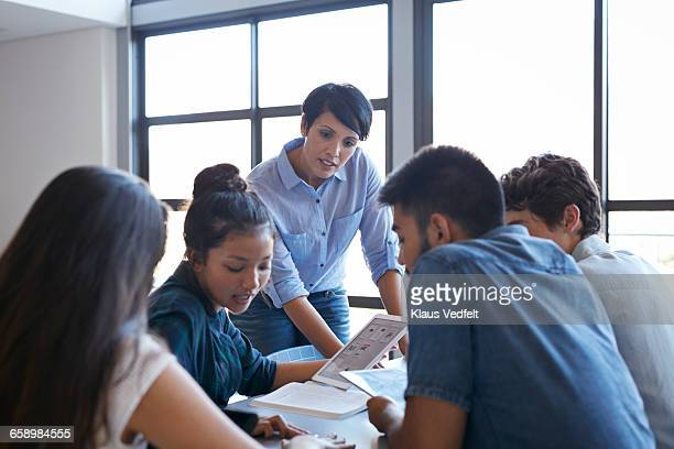 Teacher assisting students in group