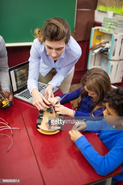 Teacher assisting students in making toy car