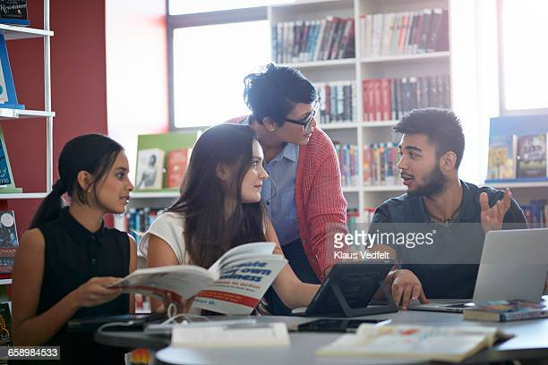 Teacher assisting students, in the library