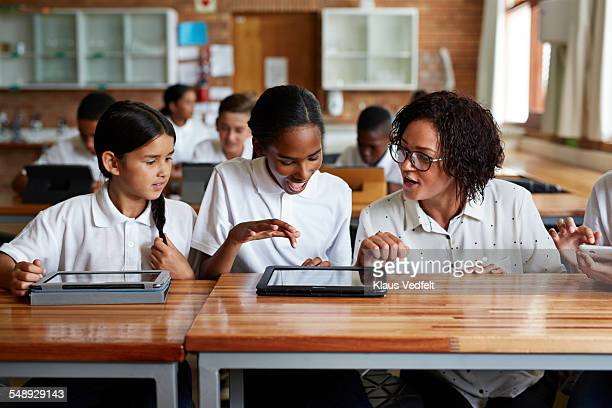 teacher assting students working with tablets - polo shirt stock pictures, royalty-free photos & images