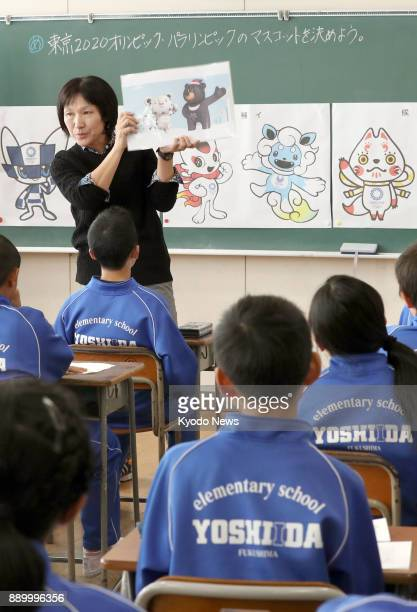 A teacher at an elementary school in Fukushima northeastern Japan leads her class in discussion on Dec 11 on which of the three pairs of candidate...