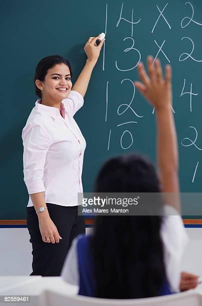 teacher at chalkboard, girl raises hand