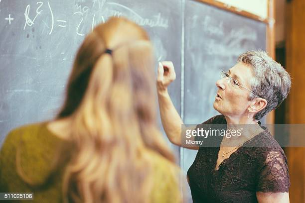 Teacher at chalkboard teaching student