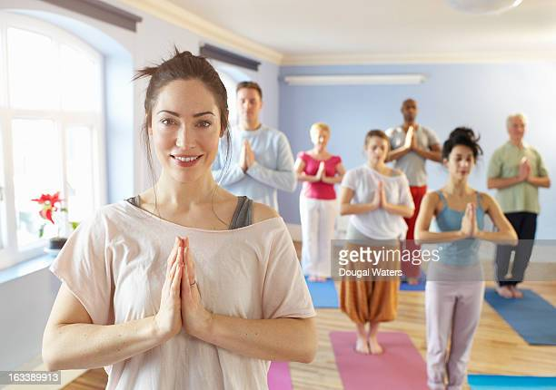 teacher at front of meditation group. - yoga teacher stock pictures, royalty-free photos & images