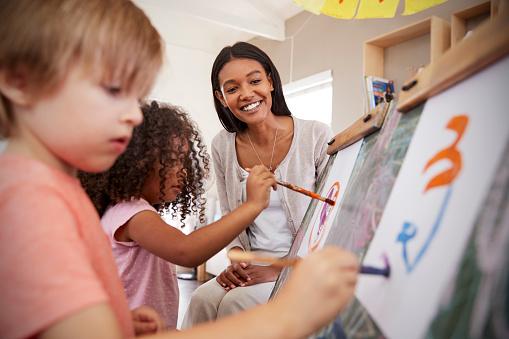 Teacher At Montessori School Helping Children in Art Class 684061980