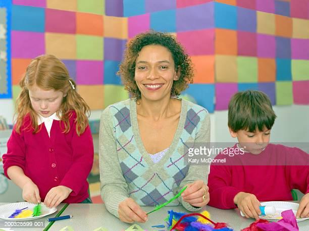 Teacher between two children (5-7) decorating paper plates, portrait