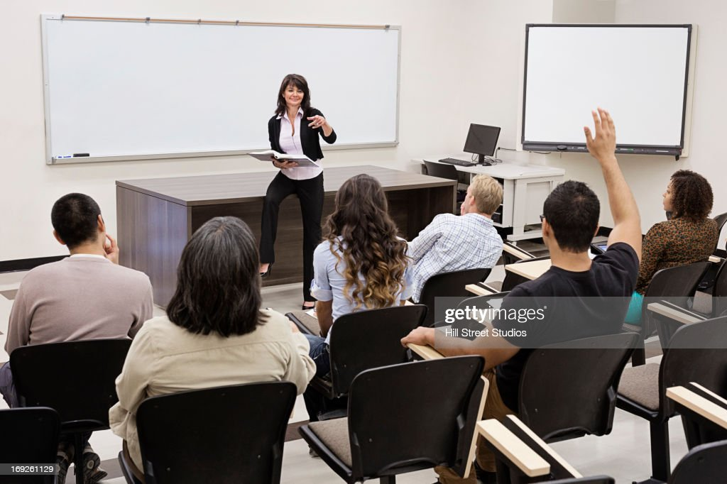 Teacher calling on students in classroom : Stock Photo