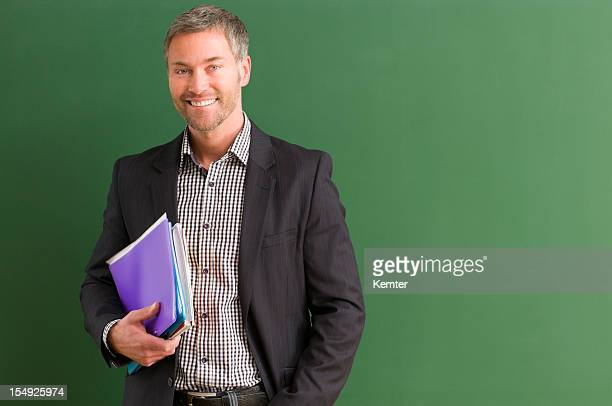 Teacher carrying books and standing by the blackboard
