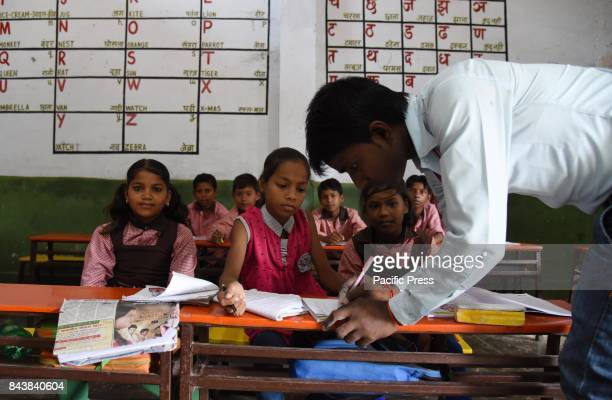 A teacher check copy of Students attend a class at a government primary school on the eve of World Literacy day in Allahabad on September 8 was...