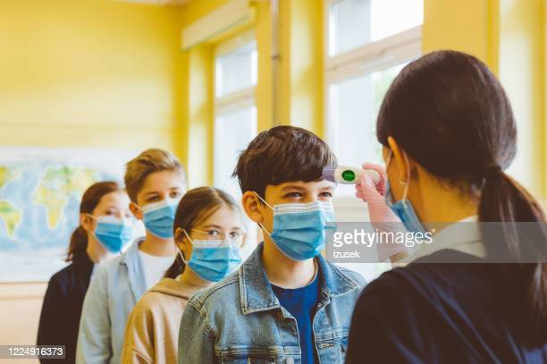 a teacher checks temperature of students at a high school - temperature checkpoint stock pictures, royalty-free photos & images
