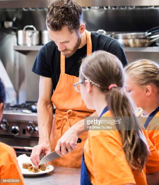 Teacher chopping food for students in kitchen