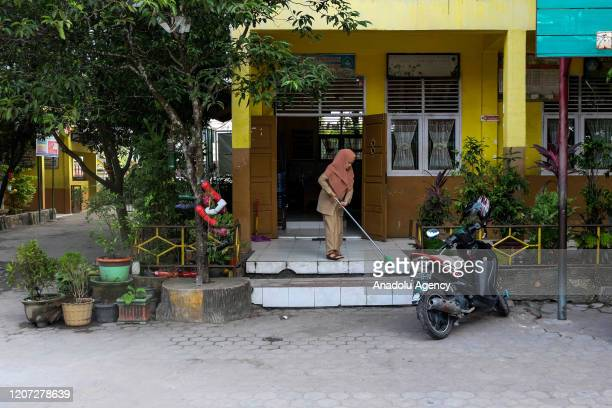 A teacher cleans the entrance of an elementary school in Pekanbaru Riau Indonesia on March 16 2020 Indonesian government instructed all educational...