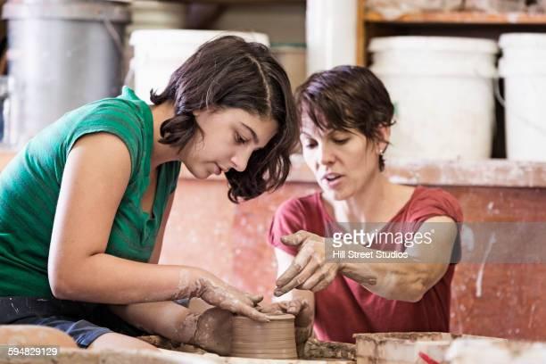 Teacher demonstrating pottery wheel for student