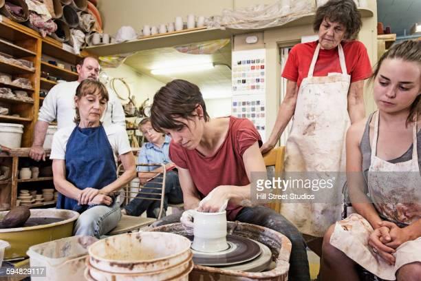 Teacher demonstrating pottery wheel for students