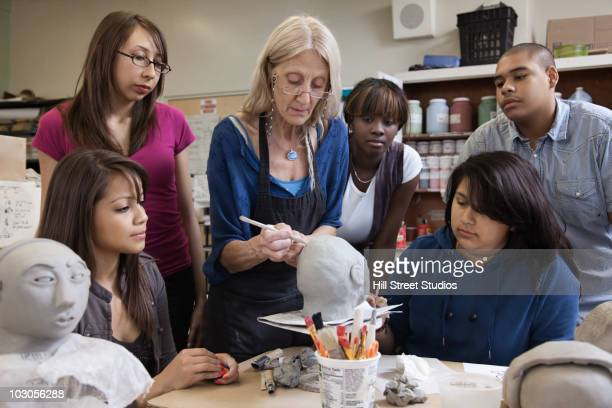 teacher demonstrating sculpting to students - la art show stock pictures, royalty-free photos & images